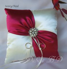 Wedding ring bearer pillow * The pillow is made with IVORY satin and is decorated with a RED satin sash and a brooch. * There is a ribbon on the back for the childs hand making it easy to carry. * Size: 8 square ♥♥Gift box and faux rings for the pillow are included.♥♥ Made in my