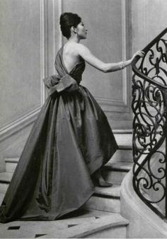 1959  Model in beautiful evening gown of violet taffeta, asymmetric neckline completely bares one shoulder, ruched bodice, large bow in back falls in train, by Givenchy,
