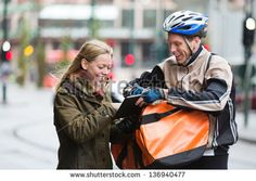 Courier delivery man with backpack showing digital tablet to young woman on street - stock photo