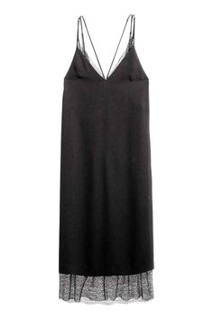 Jurk met kant: Een jurk van geweven kwaliteit met een V-hals en smalle schouderbandjes die elkaar kruisen op de rug. De jurk is…