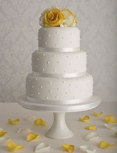 Simple and elegant traditional wedding cake with a dot theme and yellow flowers.