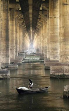 Solitude fishing under a bridge in Ganges, Allahabad, India.