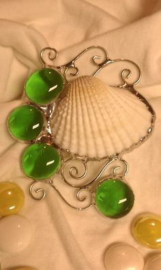 Fun and whimsical ornament for a seaside Christmas or any time of year. Made with a real shell and green glass globs, it measures about 5 inches