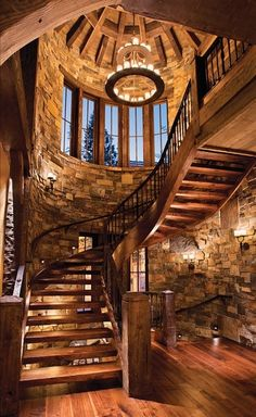 awesome staircase. great for cabin homes, love that chandelier... wood beams on the arched ceiling are amazing. stonework here is great