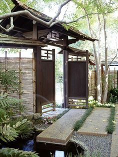 Make an Elegant Entry  A side gate to the garden opens onto a serene, shaded corner screened by a bamboo fence and paved with large slabs of concrete inlaid with rounded black stones. Tufts of deep green mondo grass soften the hardscaping.