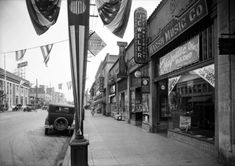 A view looking east on Santa Monica Boulevard toward Western Avenue, with the Security-First National Bank on the northwest corner (1930). To the right is the Marsh Music Company store at 5522 Santa Monica Boulevard. The flag banners suggest that it's a national holiday.