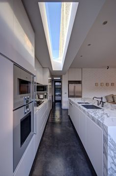 true galley kitchen in the new build known as The New Old by architect Jessica Liew in Melbourne, simple design with everything in the right place, marble counters add interest to white & grey palette