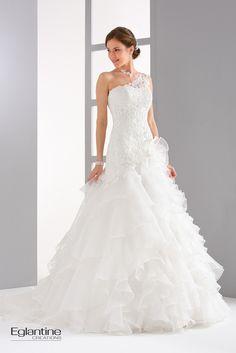 Un bustier long et une jupe à volants d'organza pour cette robe de mariée dont le buste en guipure allongera votre silhouette grâce à sa bretelle asymétrique. Votre jupe volantée en organza apporte un coté léger et vaporeux à votre robe de mariée. Boutonnage dos. Disponible en ivoire et en blanc