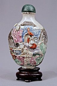 A CHINESE FAMILLE ROSE MOLDED PORCELAIN SNUFF BOTTLE