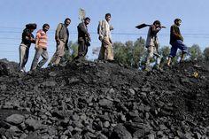 Indian laborers walked before loading coal into trucks at a warehouse in Bari Brahmana, Jammu...