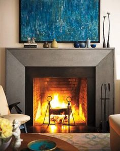 A living room fire, with grey slate surrounding, brings a warm and inviting feel to this living room. The blue and green painting above is a perfect contrast to the cool tones of the slate, lifting the look instantly. Living Room Decor Fireplace, Small Fireplace, Modern Fireplace, Fireplace Surrounds, Cozy Living Rooms, Fireplace Design, Living Room Modern, Living Room Designs, Contemporary Fireplaces