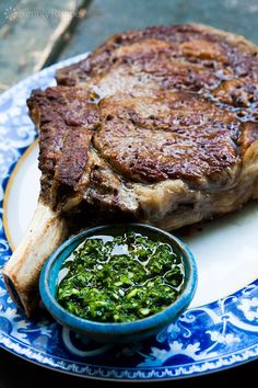 Cowboy Steak with Chimichurri Sauce ~ Frenched beef rib-eye steak seared first to brown, then cooked on lower heat to finish, served with parsley, oregano, garlic chimichurri sauce. #paleo #lowcarb On SimplyRecipes.com