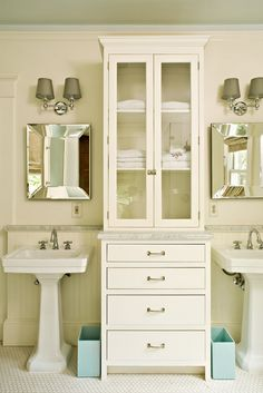 Cabinet separating wash stations + pedestal sinks + beveled mirrors + sconces + marble | Jones Pierce Architects