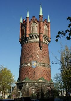 Rostock Water Tower, Germany Here stand since 1903 a water tower made of bricks in pattern style with seven stepped gables and blind windows, all rest on a base of granite. It is 60 meter ft) high building, with a diameter of 18 meters ft) in the base. Unique Buildings, Interesting Buildings, Amazing Buildings, High Building, Building Design, Beautiful Architecture, Architecture Details, Classical Architecture, Tower House