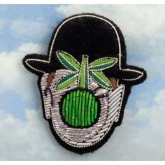 "embroidered Magritte-style ""son of man"" brooch by Arteum and Macon et Lesquoy"