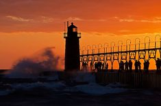Gale force winds at South Haven, Michigan attract visitors to the lighthouse and pier. by Tom Gill