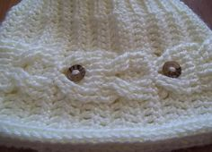 """Going Fishing, A Hat done in beautiful and classic Cables to create """"Fish"""" swimming all around the brim. A finishing touch of buttons are added to make the fish eyes."""