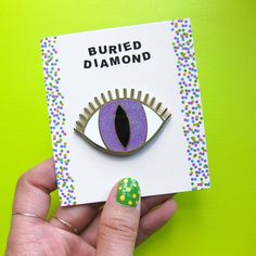MAGIC EYE BROOCH New & Improved!! This brooch is now made is beautiful, durable, gold plated metal and polished hard enamel! The colors are rich, and the pupil color has iridescent glitter in it for extra sparkle! Brooch is 1.3 tall and 2 wide. The back has two pins to help you position it just how you want it, and to hold brooch securely in place. The pin backs are yellow rubber and they hold tight! Back is embossed with Buried Diamond logo. This brooch is mounted on a paper card and…
