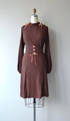 Fantastic vintage 1930s chocolate brown rayon crepe dress with mock collar, pink velvet ribbons laced through the tops of the shoulder, dramatic bishop sleeves, fitted waist, wide corset-style belt with pink velvet ribbon ties (belt has snap closures at the back, but also unties) and side metal zipper. --- M E A S U R E M E N T S --- fits like: small bust: 34-36 waist: 27 hip: up to 37 length: 40 brand/maker: n/a condition: excellent to ensure a good fit, please read the sizing g...