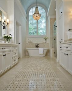 White dominates the countertops, vanities and walls in this master bathroom. Neutral tile flooring adds a touch of contrast, while an elegant chandelier and sconces illuminate the elegant space.