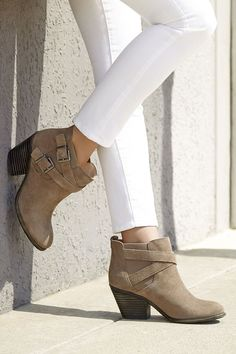 Taupe suede booties with stacked heels and crisscross buckled straps for a rugged, cool look