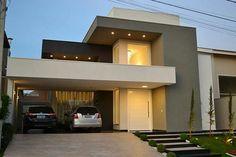 Casa com acabamento cinza, preto e branco. Spots e volumetria assimétrica, garagem lateral e jardim frontal.