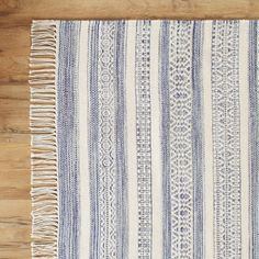 This flat-woven, cotton and wool rug is made by hand in India and features stripes of intricate pattern in navy against an ivory background.