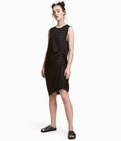 Sort/Stribet. Kropsnær kjole i kraftigt vasket bomuldsjersey. Kjolen er uden ærmer og har læg foran. Dekorativ søm bagpå i midten.