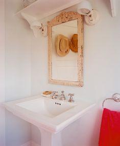 Bathroom Photo - An antique mirror hangs above a pedestal sink in a shabby chic bathroom.