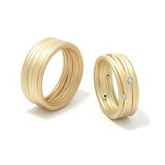 Trouwringen van Marc Lange, 'Lines', gematteerd geelgoud, bezet met witte diamanten in witgouden zetkasten.