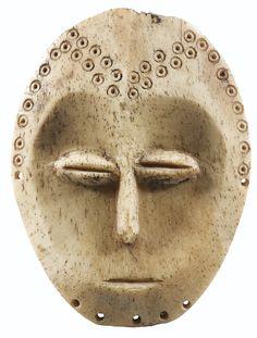 Masquette en os d'éléphant, Lega, République Démocratique du Congo | lot | Sotheby's - la très grande rareté des masquettes lukungu en os d'éléphant s'ajoute ici la sensibilité des modelés, accentuée par l'épure géométrique des traits et des motifs en chevrons. Les trous percés à la lisière du menton l'inscrivent parmi les exceptions de masquettes lukungu portant, à l'origine, une barbe en fibres végétales.