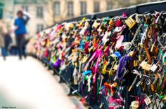 Chris and I have a lock on this bridge! True story! -lf  Pont des Arts aka Lovers Bridge Paris, France    In the romantic capital of the world, lovers fasten padlocks to the railings of the Pont des Arts bridge in Paris. The couple then toss the keys into the Seine river below, symbolizing their eternal love.