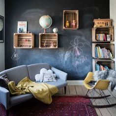 Encourage your children's creativity by designing a space where there's plenty of room to play. This bedroom has been decorated with a chalkboard paint on one wall so that children can draw to their heart's content, plus there's a sofa, rocking chair and plenty of floorspace for play