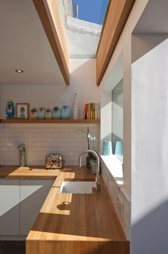 Extension One by Denizen Works - Oak was also used for the kitchen worktop, which wraps around the white cabinets, and for a chunky shelf above.