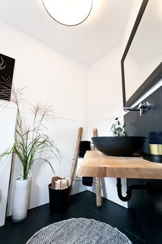 Waschtisch mit schwarzen Waschbecken und Holzplatte: rustikale Badezimmer von Banovo GmbH