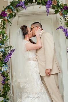 first kiss, wedding kiss, cream tux, white dress, purple arch, purple flowers, fit and flare dress, wedding dress, cream sash, mermaid dress,