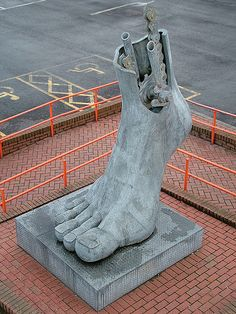 'Footplate', from the pedestrian bridge, Flint railway station, North Wales, UK .a Brian Fell's 3m tall sculpture, installed in 1999, celebrates Flint's location at the start of a number of National Cycle Network routes, which also explains the bike mechanism in the ankle.