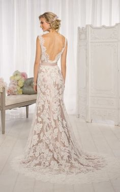 This stunning form-fitting gown features a blush satin underdress and a delicate lace overdress.