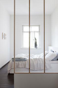 Une chambre minimalisté avec des draps en lin lave et une verrière