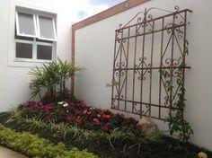 A antiga grade de janela, aqui foi usada como treliça para apoiar a trepadeira, criando um jardim personalizado.
