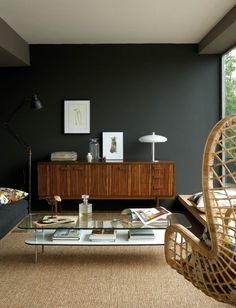a contemporary living room with dark gray/green walls