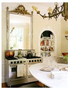 large vintage mirror above the stove and large copper pot.