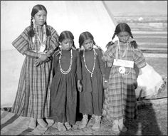 Four lovely girls strike a pose, and it appears somewhat reluctantly, standing in front of a teepee on the Flathead Indian Reservation in western Montana. This photograph was taken in 1905.