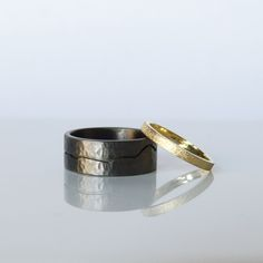 Black rhodium plated sterling silver hammered gents wedding ring. 18ct yellow gold ladies textured square wedding ring
