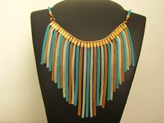 Maxi colar com franjas de corrente Rabo-de-Rato nas cores azul turquesa, dourado e prateado. Atrás fecho lagosta com corrente extensora. R$65,00