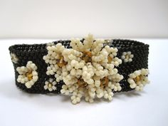 Couture peyote beaded cuff in black and ivory with antique daisies and sunflower crystals. £230,00, via Etsy.