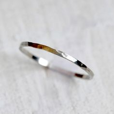14k gold hammered band. A thin hammered wedding ring or everyday ring. Delicate but strong and can be worn as a single ring or stacked. This listing is for ONE ring. The ring measures about 1.2mm wide