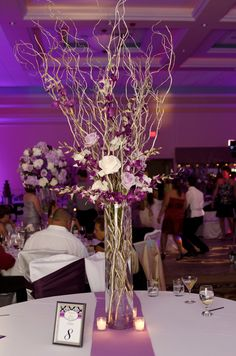 A tall glass fusion centerpiece consisting of curly willow, accents of purple dendrobium, white and lavender roses.