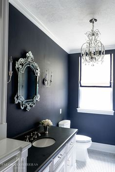 Black and white bathroom features bold black walls accented with white crown molding framing Venetian mirror flanked by Huntingdon Crystal Double Sconces over white washstand topped with honed black countertop situated next to toilet and window dressed in white roman shade with black grosgrain trim.