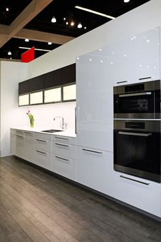 Simple, elegant black and white kitchen cabinets, upper glass cabinets with integrated lighting.